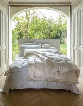 Weisses Bett auf Parkettboden und Blick aufs Grüne von Gute N8!