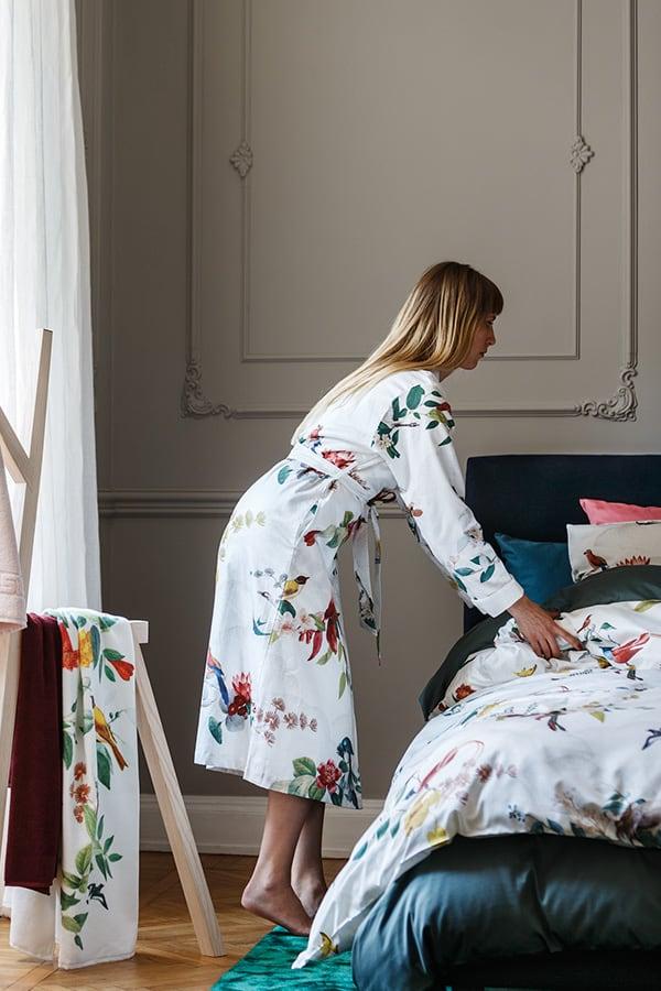 Blonde Frau in Bademantel von Gute N8! neben ihrem Bett